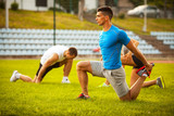 Young people exercising on sport field.They standing on grass and stretching.Man in blue shirt are in focus.