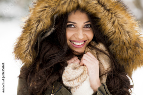 Young woman with a fur hood in the park on the snow Plakát