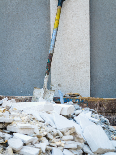 Poster Spade in pile of rubble.