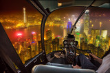 Helicopter cockpit flying on Hong Kong skyline with glowing signboards at night in Victoria Harbour, Hong Kong island. Concept of transport, travel and business.