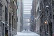 Street of Old-Montreal in winter under a snow storm with a modern skyscraper in the background
