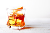 Glass of old fashioned whiskey with ice, orange and cherries over a white wood table - 134519806