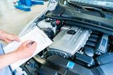 Mechaniker kontrolliert Auto mit Checkliste in Kfz-Werkstatt  - 134568463
