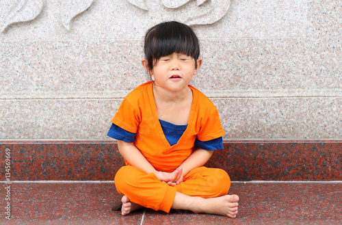 Kid girl in Shaolin monk orange clothes doing meditative tai chi exercise on Karate martial art sports training in chinese temple in thailand Poster