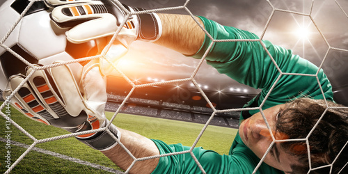 Fotobehang Voetbal Goalkeeper catches the ball in the stadium
