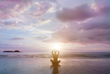 Fototapety Person is sitting in beautiful sunset sea beach, he is reflected in wet sand.Young man make meditation in lotus pose, yoga, zen and wellness concept.