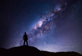 Milky Way landscape. Silhouette of Happy man standing on top of mountain with night sky and bright star on background. - 134590603