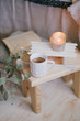 Still life details of interior: knitted clothes on a vintage wooden floor, cup of tea, candles and book