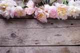 Border from tender pink  peonies flowers on aged wooden backgrou - 134622012
