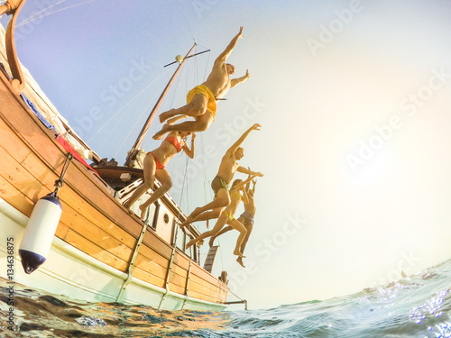 Poster Happy friends diving from sailing boat into the sea