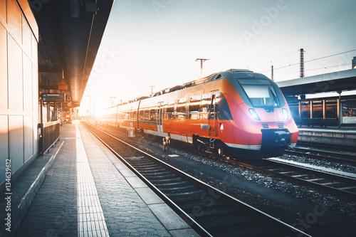 Nowożytna wysoka prędkość czerwona kolejka przy stacją kolejową przy zmierzchem. Włączanie świateł pociągu. Linia kolejowa z rocznika tonowaniem. Pociąg na peronie kolejowym. Krajobraz przemysłowy. Turystyka kolejowa