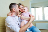 Baby with mom and dad smiling laughs in the room