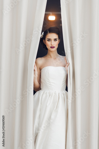 Poster Stylish bride in wedding dress standing near the curtains