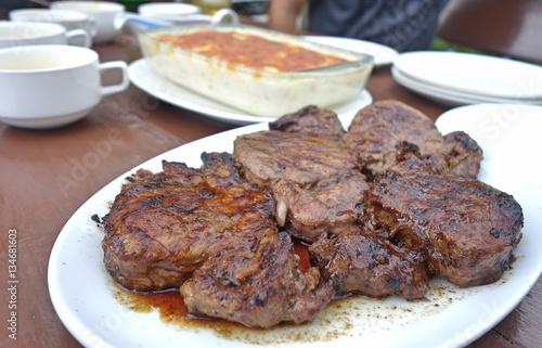 beef steak on plate at outdoor table. Poster