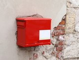 red mailbox on the peeling wall
