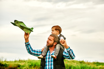 Father and son playing with toy plane