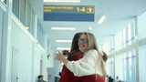 Women meeting and hugging on the airport, slow motion