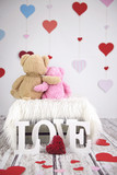 Two toy teddy bears sitting in front of hearts - 134695294
