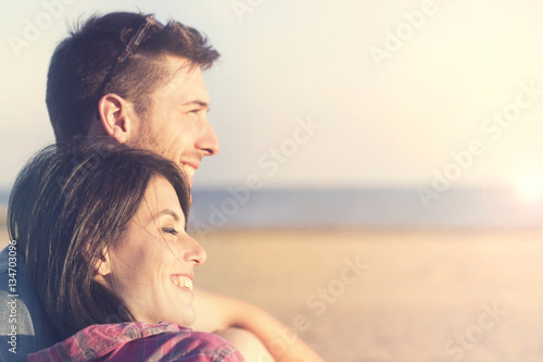 Poster couple smiling talking in front of the sunset