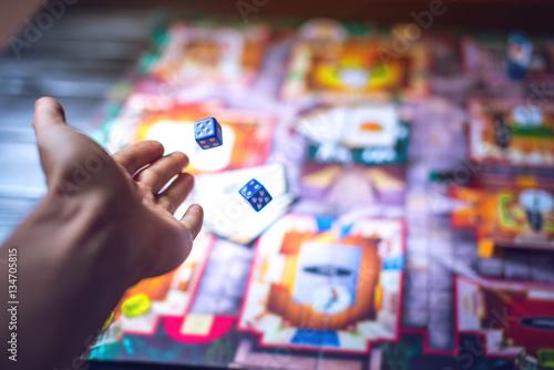 Ręka rzuca kostką na tle gier planszowych