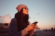 Portrait of a lovely girl in eyeglasses holding mobile phone