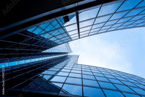 Modern and visionary skyscraper with many windows and reflections and blue sky
