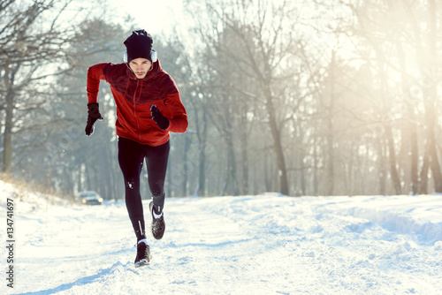 Fototapeta Sportsman Running in Extreme Snow Conditions. Intensive Training Outdoors.