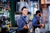Fototapety Girl barista bartender waiter in uniform making coffee at the bar.