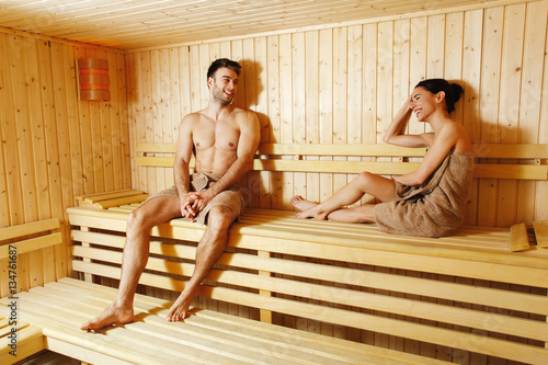 Attractive young couple relaxing in sauna