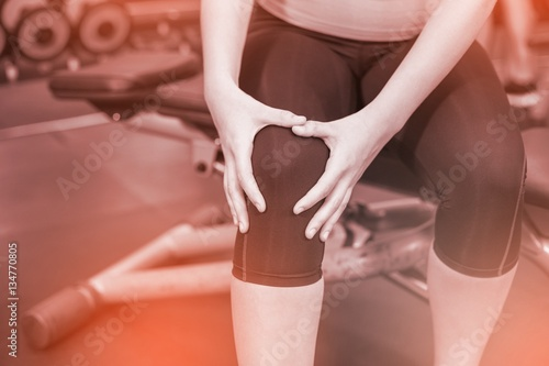 Midsection of fit woman having knees pain