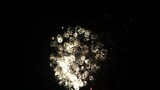 Fireworks in bright colours in the night sky on New Years Eve with ambient audio