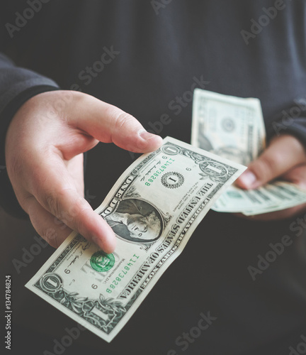 Man giving money one us dollar banknote and holding cash in hands. Money credit