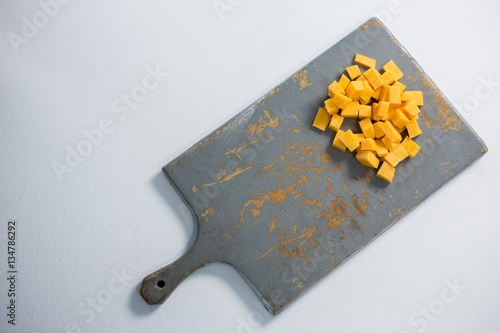 Cheddar cheese slices on cutting board