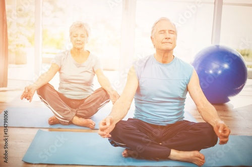 Senior couple meditating at home