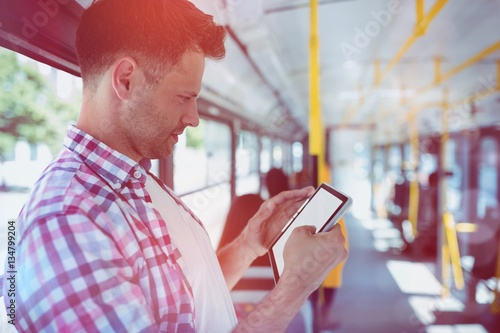 Poster Handsome man looking at digital tablet in bus