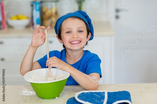Poster Smiling boy mixing cookie dough in kitchen