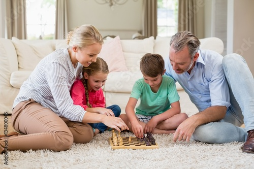 Poster Family playing chess together at home in the living room