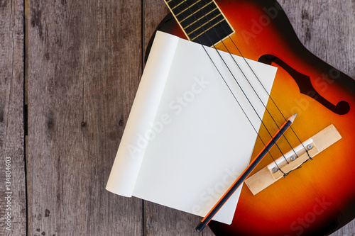 Ukulele and Paper Notes on Wooden background