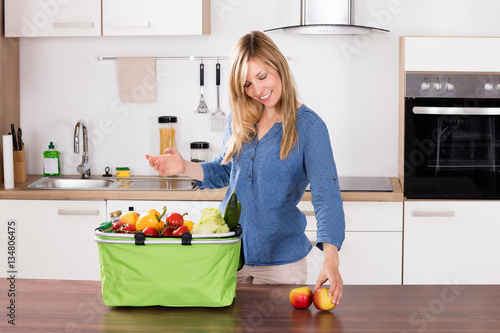 Poster Smiling Woman Removing Apples From Grocery Bag