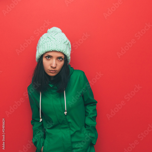 Brunette in hat and coat. Only green and red. Hipster style. Minimalism