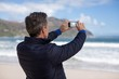 Mature man photographing scenery using cell phone