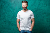 Fototapety Man in the white t-shirt with space to copy paste standing on the green wall background.