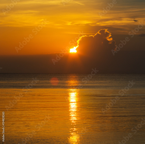 Poster Sun in the clouds above the seascape with mirror reflection