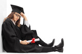Depressed graduate student with a diploma sitting on the floor
