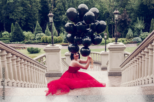 Poster Beautiful fashion young woman in gorgeous red dress and crown holding black ball