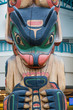 Colorful Totem Pole with Modern Building in Background