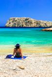 Girl on the beautiful beach Kounoupa in Astypalea island, Greece
