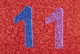 Number eleven blue purple color over a red background. Anniversa
