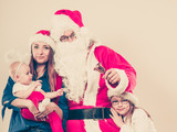 Mother, Santa and two daughters christmas family photo