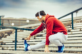 Young fitness man runner stretching legs before running on the s